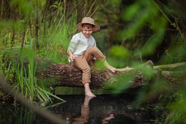De jongen van de babyjongen in rustieke kleren en rieten hoed zit met een hengel in zijn handen en vangt vissen op een logboek over de rivier. hobby's en vrije tijd voor mannen.