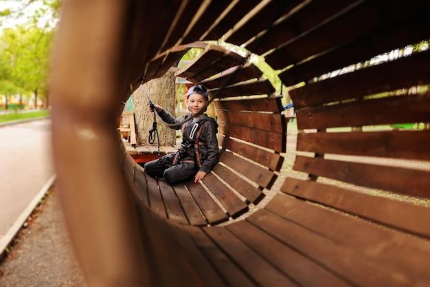 De jongen van de kindkleuter is een hindernis in een hoog touwcursus van de veiligheidsalpinism apparatuur