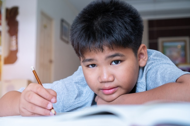 De jongen van de portret aziatische student legt het leggen van zijn thuiswerk op notitieboekje terwijl het leren van studie