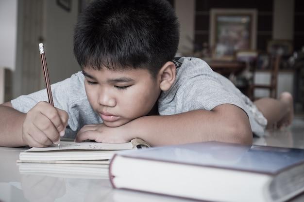 De jongen van de portret aziatische student legt thuis zijn huiswerk op notitieboekje terwijl het leren langs