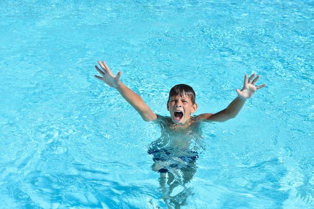 De jongen verdrinkt in het water in het zwembad of in de zee en roept om hulp