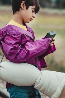 De jongen verloor in het bos op een regenachtige dag die door gps met zijn gps-telefoon probeert te communiceren