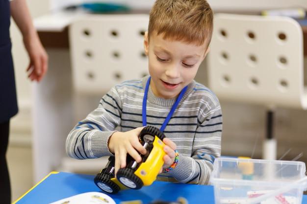 De jongen verzamelt een model van een radiografisch bestuurbare auto