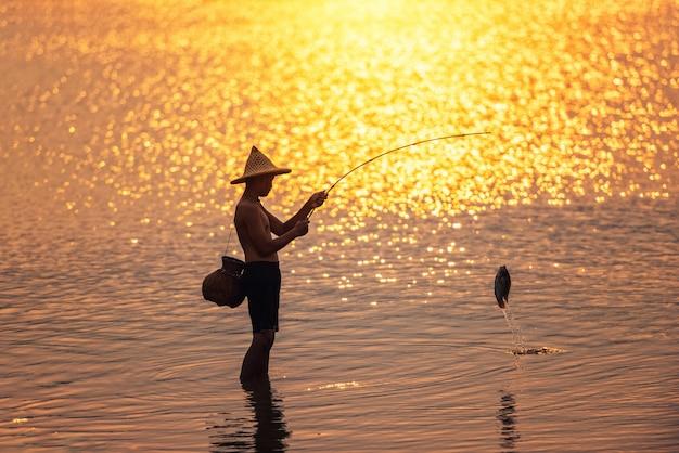 De jongen vist bij zonsondergang op het meer