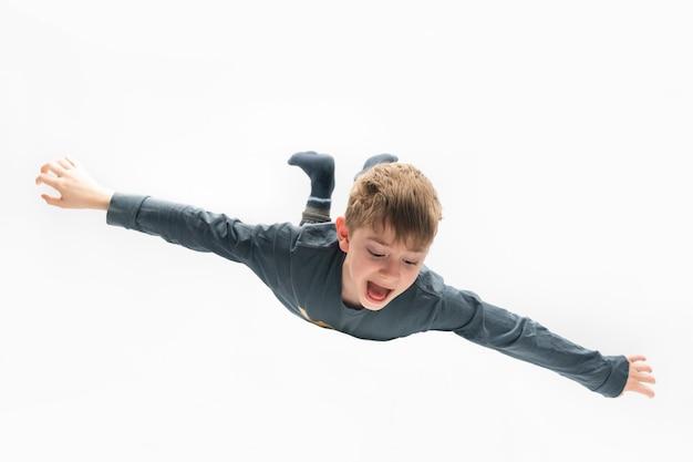 De jongen vliegt als een vliegtuig dat op wit oppervlak wordt geïsoleerd