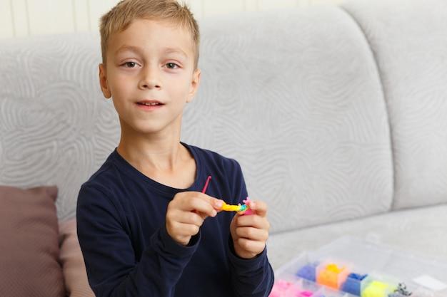 De jongen weeft armband van rubberringen thuis op de bank