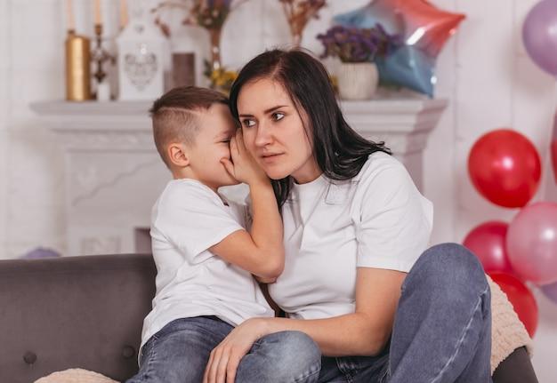 De jongen zegt iets geheims in het oor van zijn moeder