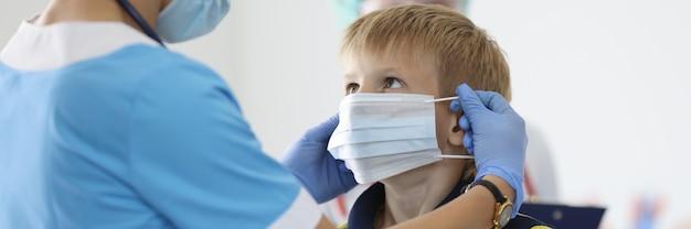 De jongen zet beschermend medisch masker in artsenbureau op