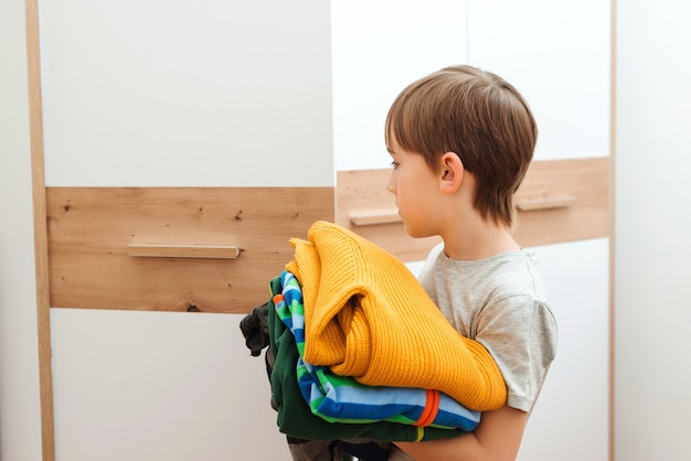 De jongen zet orde op zaken in de kast. een stapel kleurrijke kleren. kid organiseren van kleding in kledingkast.