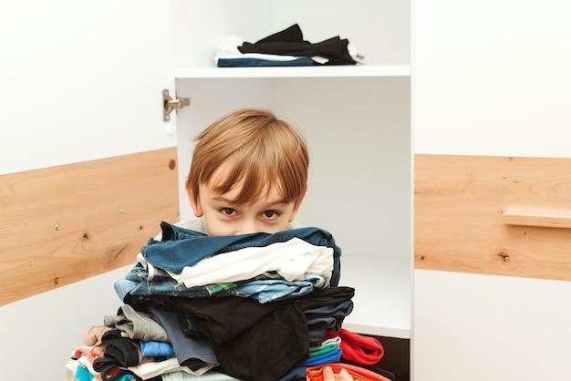 De jongen zet orde op zaken in de kast. een stapel kleurrijke kleren.