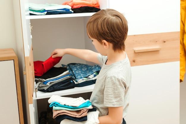 De jongen zet orde op zaken in de kast. kid organiseren van kleding in kledingkast. bestel in de kast.