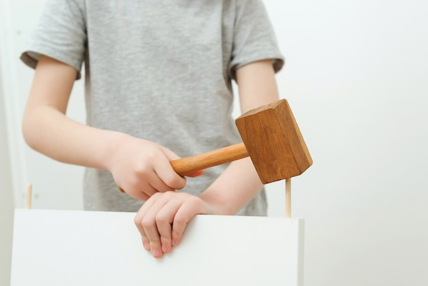 De jongen zet zelf een boekenplank in elkaar. vader en zoontje die thuis meubels monteren.