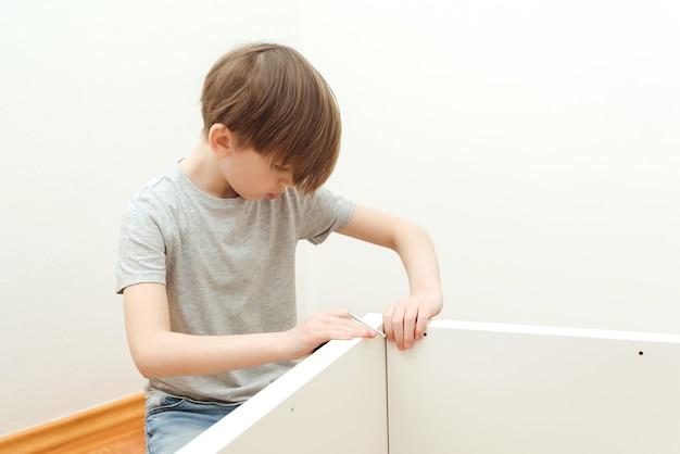 De jongen zet zelf een boekenplank in elkaar