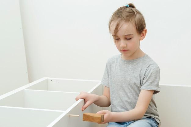 De jongen zet zelf een boekenplank in elkaar.