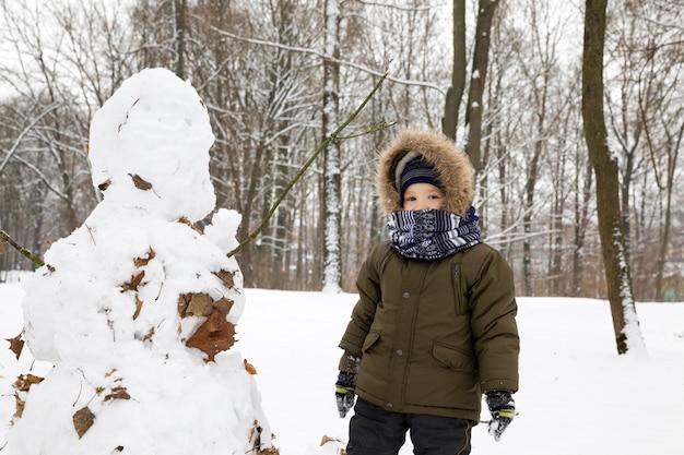 De jongen zette zijn sneeuwpop in winterpark, van de sneeuwman die uit een groot aantal gevallen bladeren steekt, verblijft buiten in het park