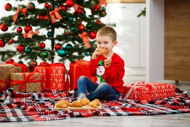 De jongen zit bij de kerstboom in de kerstkeuken. houdt een croissant in zijn handen. gezellige winteravonden in huis. er liggen veel kerstcadeaus onder de boom