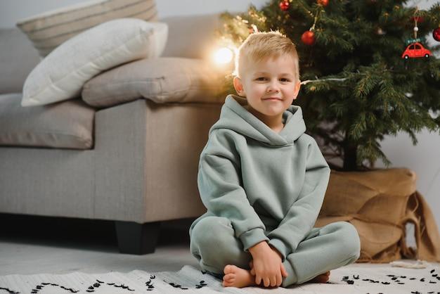 De jongen zit in de buurt van de kerstboom met geschenken. kinderen voor de kerstvakantie.