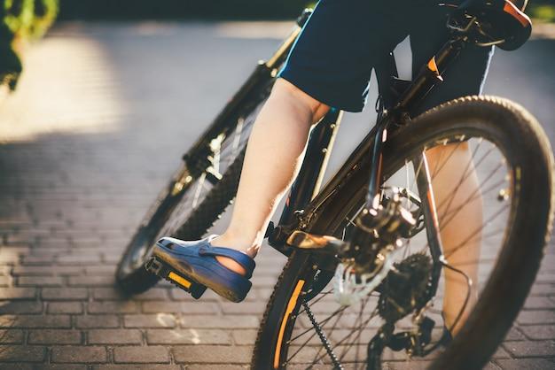 De jongen zit op de fiets