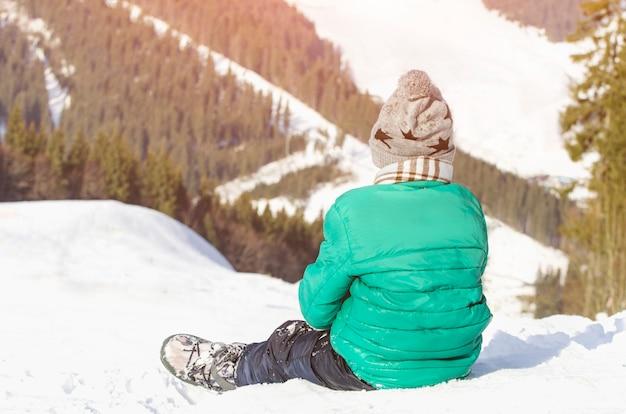 De jongen zit op een met sneeuw bedekte heuvel op de achtergrond van dennenbos en bergen.