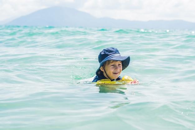 De jongen zwemt in de zee