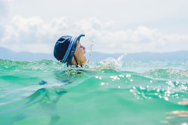 De jongen zwemt in de zee.