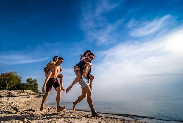 De jongens dragen meisjes op hun schouders en rennen op het strand