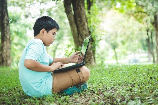De jongens studeren basisschool, dragen een bril, kijken naar zwarte notebookcomputers op het grasveld in de tuin.