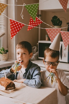 De jongens vieren hun verjaardag. parafernalia van de verjaardag van kinderen. broers bedekt met cake op hun gezicht. familiefeest thuis