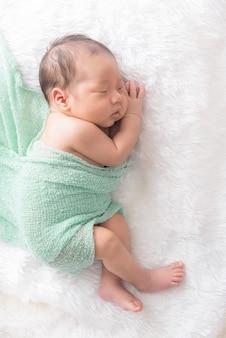 De jongensslaap van de baby op een witte wikkeldoek het feelgood ontspannen