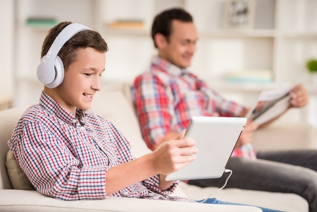 De jongenszitting thuis bij bank en luistert naar muziek.