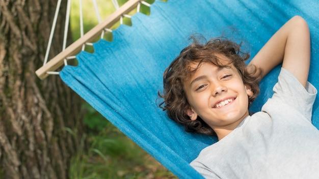 De jongenszitting van smiley in hangmat