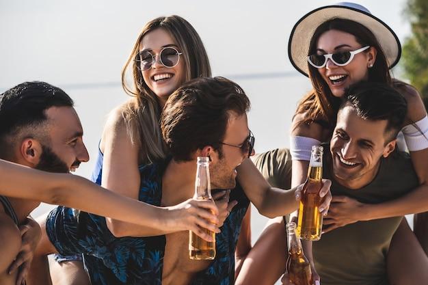 De jongeren met flessen genieten van de zomer op het strand