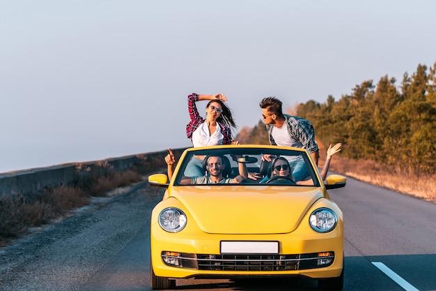 De jongeren reizen in een gele cabriolet