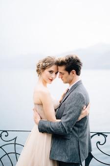 De jonggehuwden knuffelen dichtbij een smeedijzeren hek tegen het comomeer