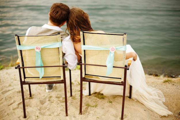 De jonggehuwden koppelen zitting dichtbij water op het strand