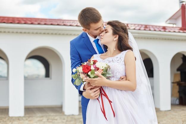De jonggehuwden omhelzen en kussen dichtbij vuurtoren bij huwelijk