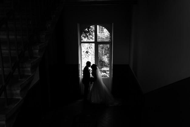 De jonggehuwden silhouetteren dichtbij een hoog venster in een trap van de oude bouw