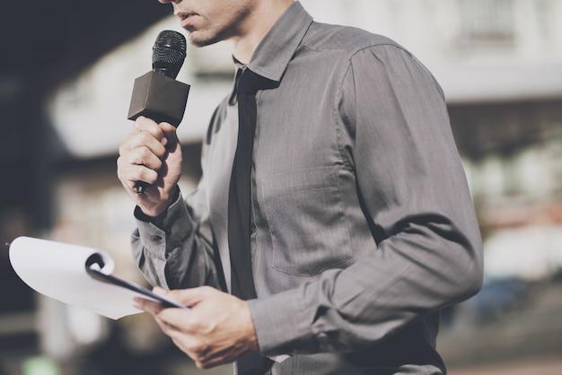 De journalist spreekt in de microfoon