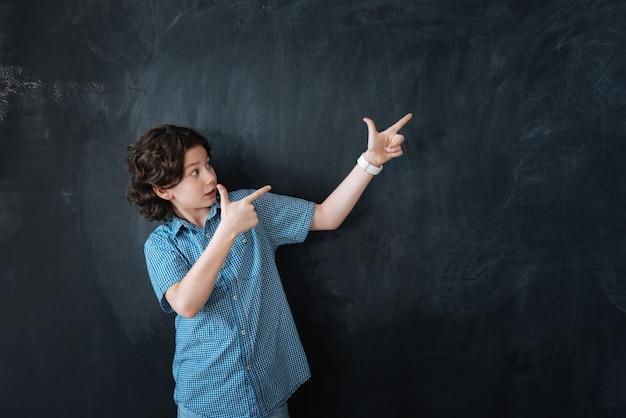 De juiste keuze maken. handige speelse creatieve jongen die tegen het bord staat en geniet van een denkbeeldige tekening terwijl hij naar boven wijst