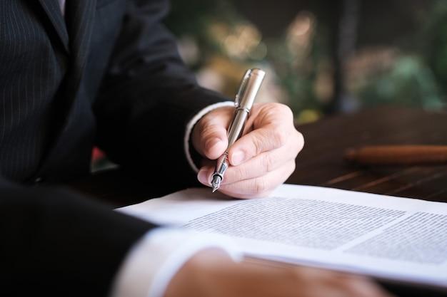 De juridisch adviseur biedt de cliënt een ondertekend contract met de voorzittershamer en de juridische wetgeving aan. justitie en advocaat concept.