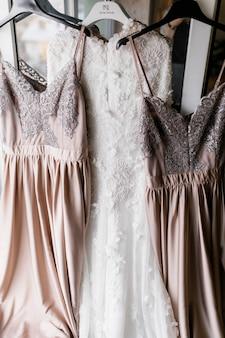 De jurk van de bruid en haar twee bruidsmeisjesjurken hangen aan hangers