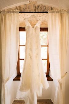 De jurk van de bruid hangt aan de kroonlijst voor het raam.
