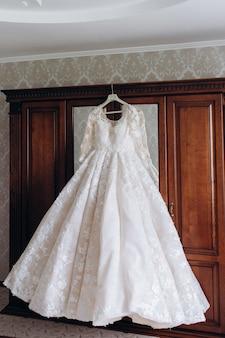 De jurk van de bruid hangt aan een kledingkast