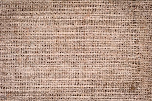 De jute geweven achtergrond van het textuurpatroon in lichte room beige bruine kleurentoon