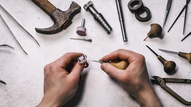 De juwelier controleert de sterkte van het bevestigen van een steen in een gouden ring