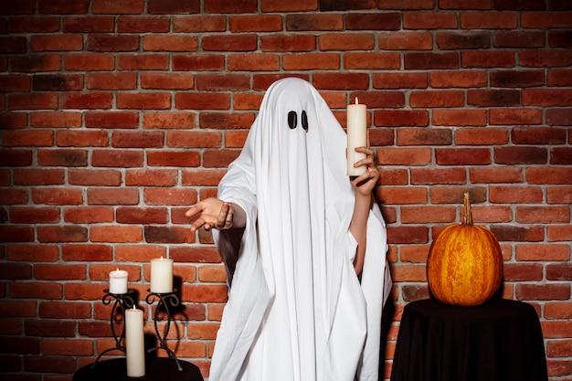 De kaars van de spookholding, die hand uitrekken aan. halloween feest.