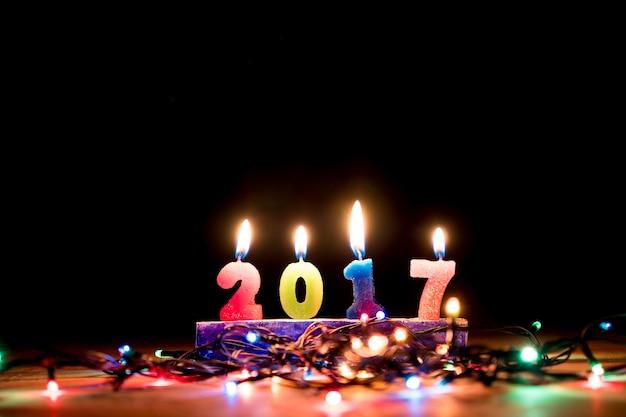 De kaarscijfers van 2017 met kerstmislichten op zwarte achtergrond. nieuwjaarsconcept