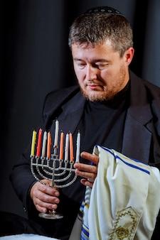 De kaarsen van de de handverlichting van de mens in menorah op lijst die voor hanukka wordt gediend