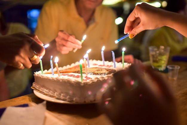 De kaarsen van de de handverlichting van de moeder in verjaardagscake