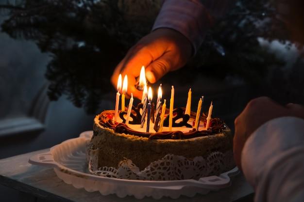 De kaarsen van de vaderhandverlichting in verjaardagscake